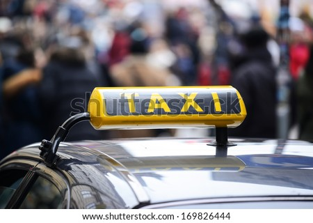 Taxi car in town centre crowded with pedestrians - stock photo