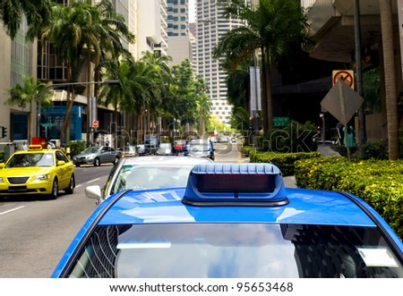 Taxi in the central sreet in Singapore. Sharpness on a blue car