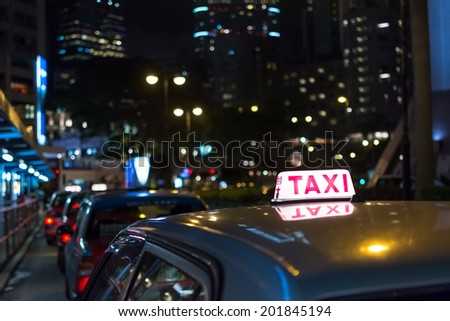 """Taxi in the night, Hong Kong, Asia. The Chinese words in the top of car is meaning """"taxi"""". - stock photo"""