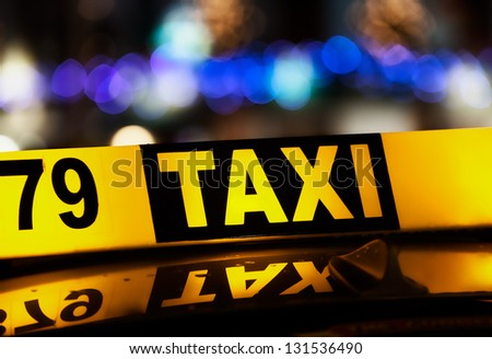 Taxi sign and blurred city lights at night - stock photo