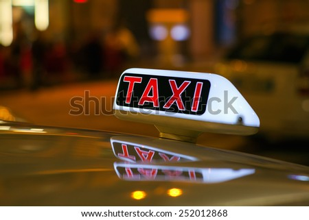 Taxi sign from parked taxi in the Milan street at night - stock photo