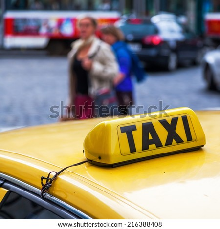 taxi sign of a taxi in Prague with crossing people in the blurred background