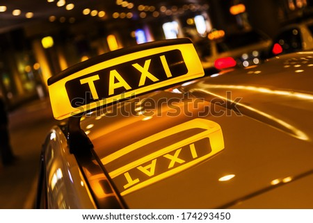 taxi sign on a car roof at night - stock photo