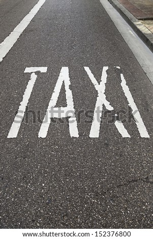 Taxi sign on the road, detail of a text signal in soil, urban transport