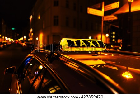 taxi sign on the roof of a taxi at night - stock photo