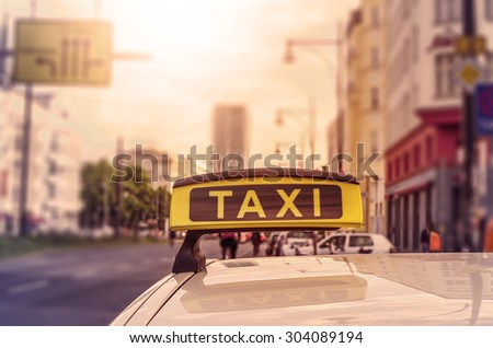 Taxi sign on top of a german cab in the evening sun, intentional selective focus - stock photo