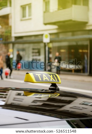 Taxi sign waiting for customers in city with defocused pedestrians and buildings