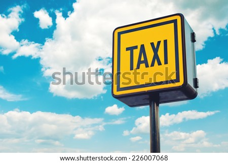 Taxi Stop Illuminated yellow Sign with blue sky in background - stock photo
