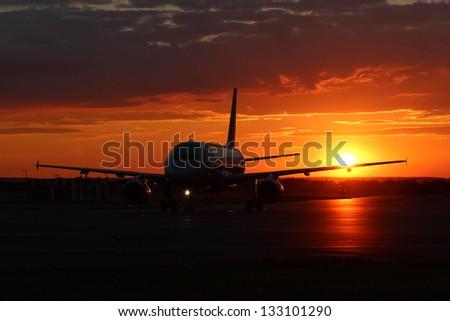 Taxiing aircraft at sunset - stock photo