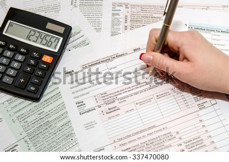 Taxpayer filling out US tax form 1040 - stock photo