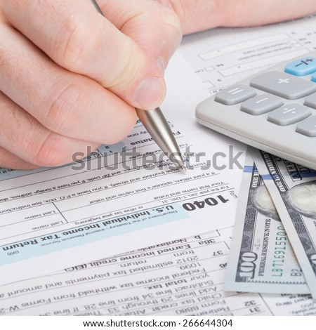 Taxpayer filling out USA 1040 Tax Form - close up shot - stock photo
