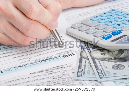 Taxpayer filling out USA 1040 Tax Form - studio shot