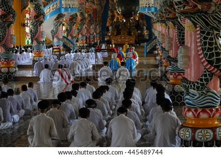 TAY NINH, VIETNAM - JUNE, 16, 2015: People praying in a Caodai temple in Vietnam