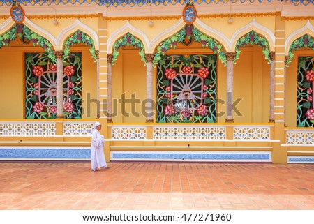 TAY NINH, VIETNAM - NOV 10, 2014:Cao Dai temple area and meditating followers of the Cao Dai religion in the temple Cao Dai