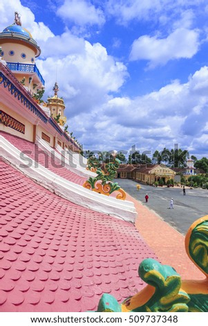 TAY NINH, VIETNAM - October 23, 2016:roof of Cao Dai temple area and meditating followers of the Cao Dai religion in the temple Cao Dai