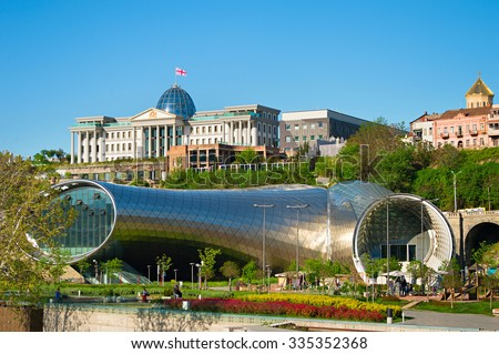 TBILISI, GEORGIA - MAY 01, 2015: People in apark in front of Concert Hall and the Official residence of Georgian President in Tbilisi, Georgia - stock photo