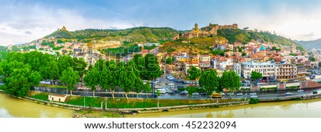 TBILISI, GEORGIA - MAY 28, 2016: The wide panoramic view of Tbilisi old town center, Narikala Fortress and Tabor Monastery on the distant hill, on May 28 in Tbilisi. - stock photo