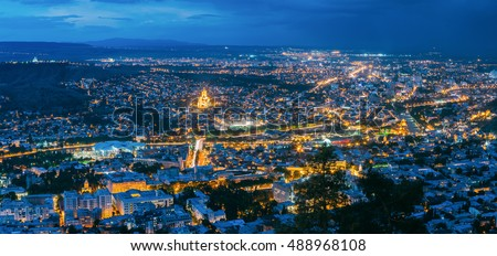 Tbilisi, Georgia. The Scenic Panoramic Top Field Of Vision. Cityscape In Evening Illumination With All Famous Landmarks And Sights Under Dramatic Blue Sky With Moon Background.