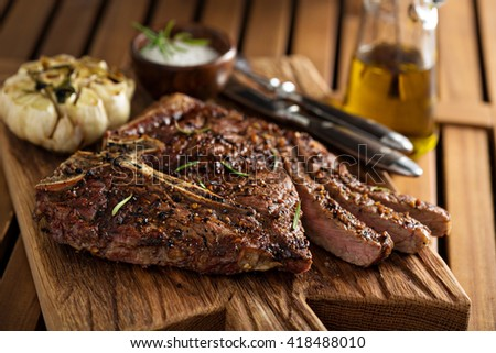 Tbone beef steak cooked on a grill with rosemary and garlic - stock photo