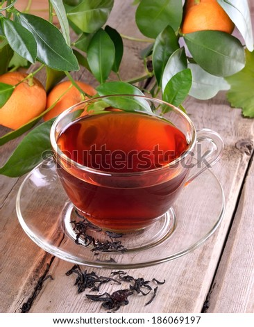 Tea and branch of tangerines on wooden table