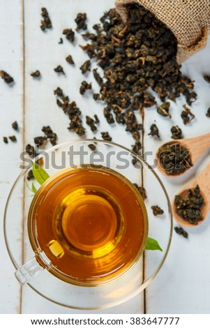 Tea and leaves tea on white wooden background