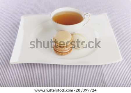 Tea and macaroons displayed on a white plate