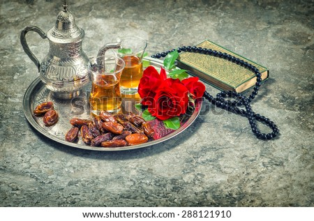 Tea and red rose flower, holy book quran and rosary. Islamic holidays decoration. Ramadan kareem. Eid mubarak. Oriental hospitality concept. Vintage style toned picture - stock photo