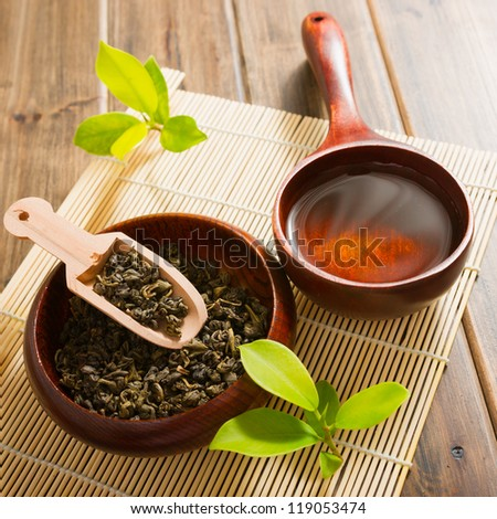tea and tea leaves on bamboo mat on wooden table