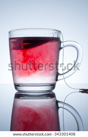 tea bag in a transparent mug with beautiful abstract stains in water with reflection on a grey background - stock photo