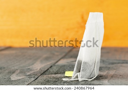 Tea bag shown in the background of stained wood - stock photo