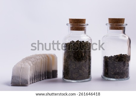 Tea bags and leaf tea in glass bottles - stock photo