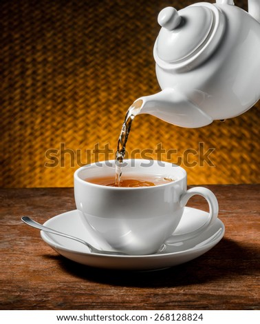 Tea being poured into tea cup - stock photo