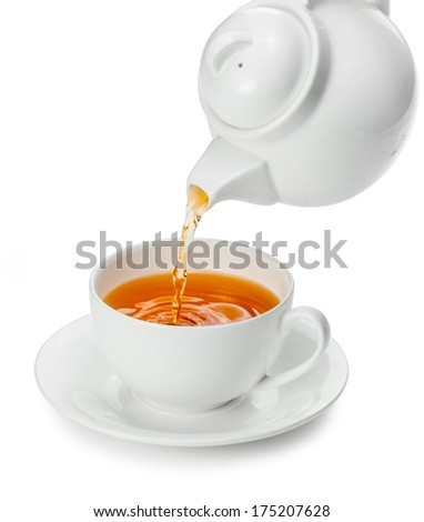 Tea being poured into tea cup isolated on a white background - stock photo
