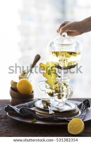 Tea Ceremony. Winter Warming Drink. Green Tea with Ginger, Honey, Lemon in Glass on Metal Tray. Inflowing From Kettle.