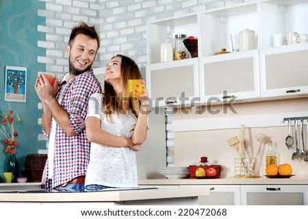 Tea ceremony. Young couple in love drinking hot tea while standing and cooking in the kitchen clamps to each other and laughing at each other - stock photo