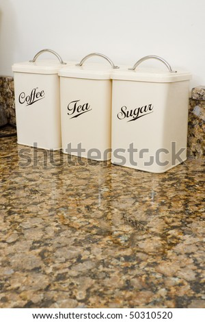 Tea, coffee and sugar pots in a modern kitchen interior with granite worktop and cream units - stock photo