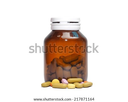 Tea colored medicine bottle with some tablets vitamins isolated on white - stock photo
