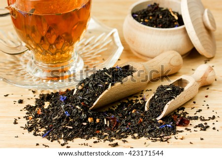 Tea composition with cup of tea and dried tea in wooden scoops on wooden background selective focus - stock photo