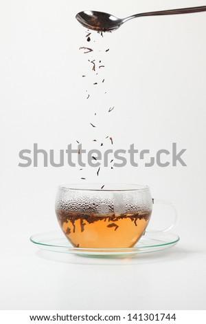 Tea crumbs falling in hot water - stock photo