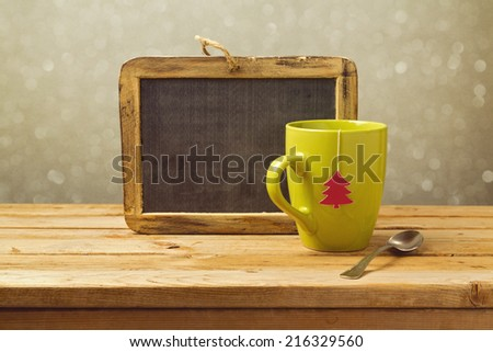 Tea cup and chalkboard on wooden table. Christmas background - stock photo