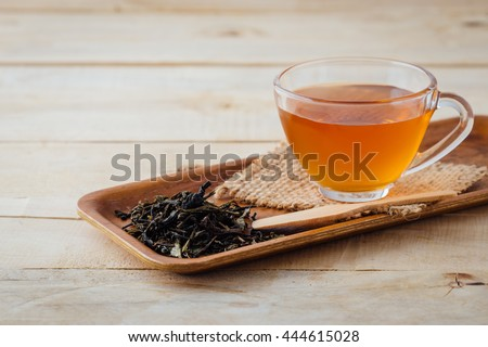 tea cup and dried tea leaves on wooden background