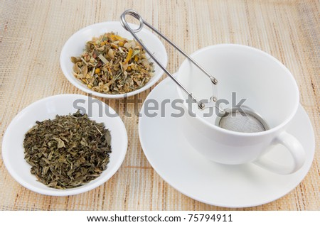 Tea cup and herbal teas on a natural matting. - stock photo