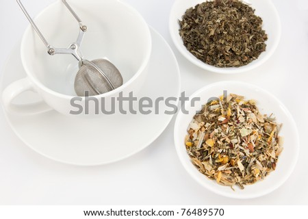 Tea cup and herbal teas on a white background - stock photo