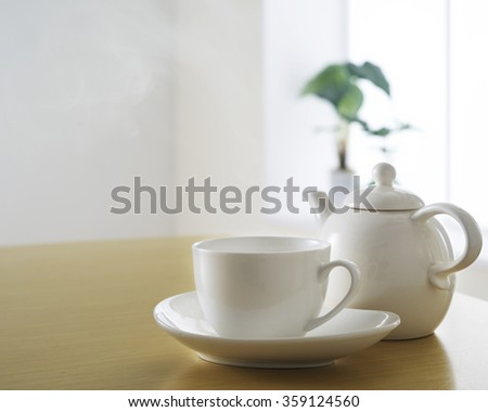 tea cup and tea pot on wooden table