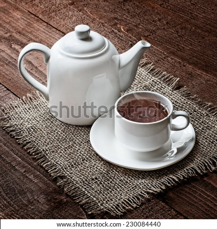 tea cup and  teapot with on the old wooden table  in winter frosty day - stock photo