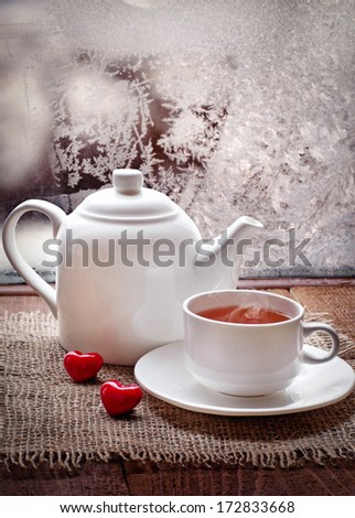 tea cup and  teapot with red hearts on old wooden table  in winter frosty day - stock photo