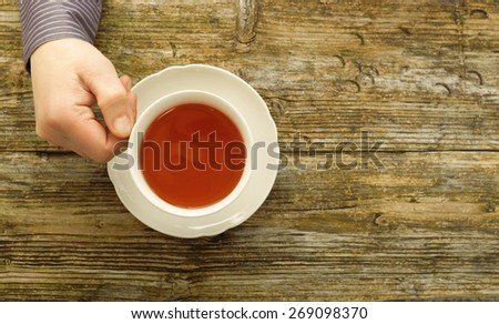 tea cup male hand holding cafe table wooden tint top view - stock photo