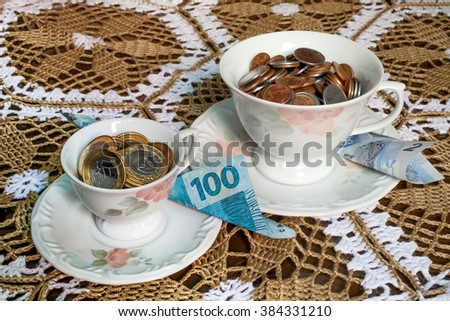 Tea cup with brazilian money inside - stock photo