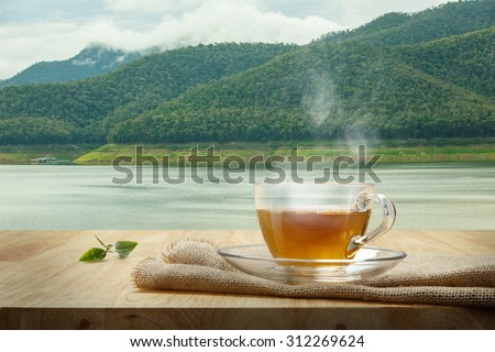 Tea cup with burlap on the wooden table and the swamp background - stock photo