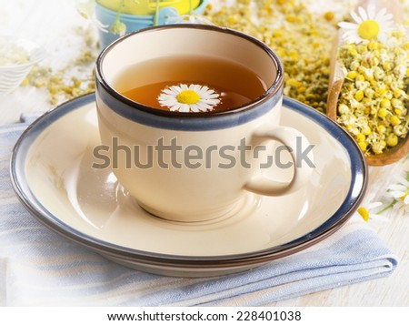Tea cup with chamomile flowers. Selective focus - stock photo